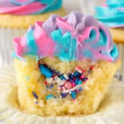 sliced open unicorn cupcake with sprinkles inside