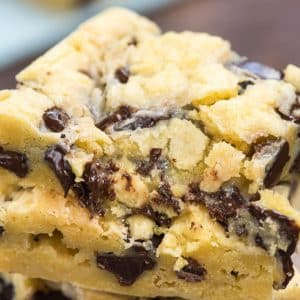 stack of chocolate chip gooey cake bars with bite missing