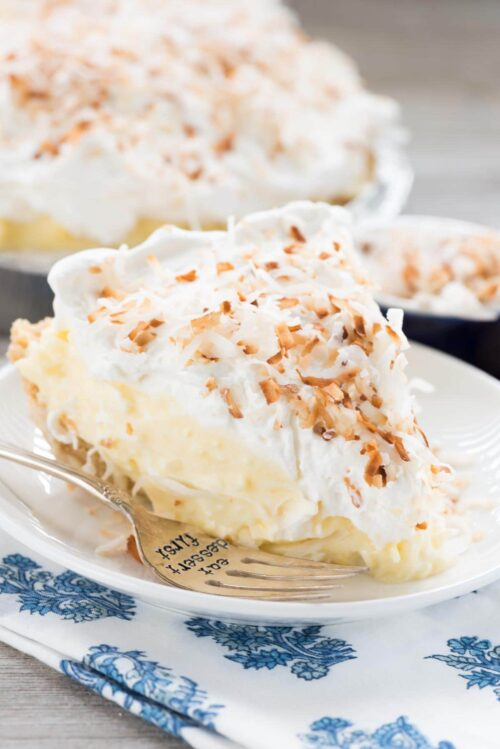Slice of Coconut Cream Pie on a white plate with a fork