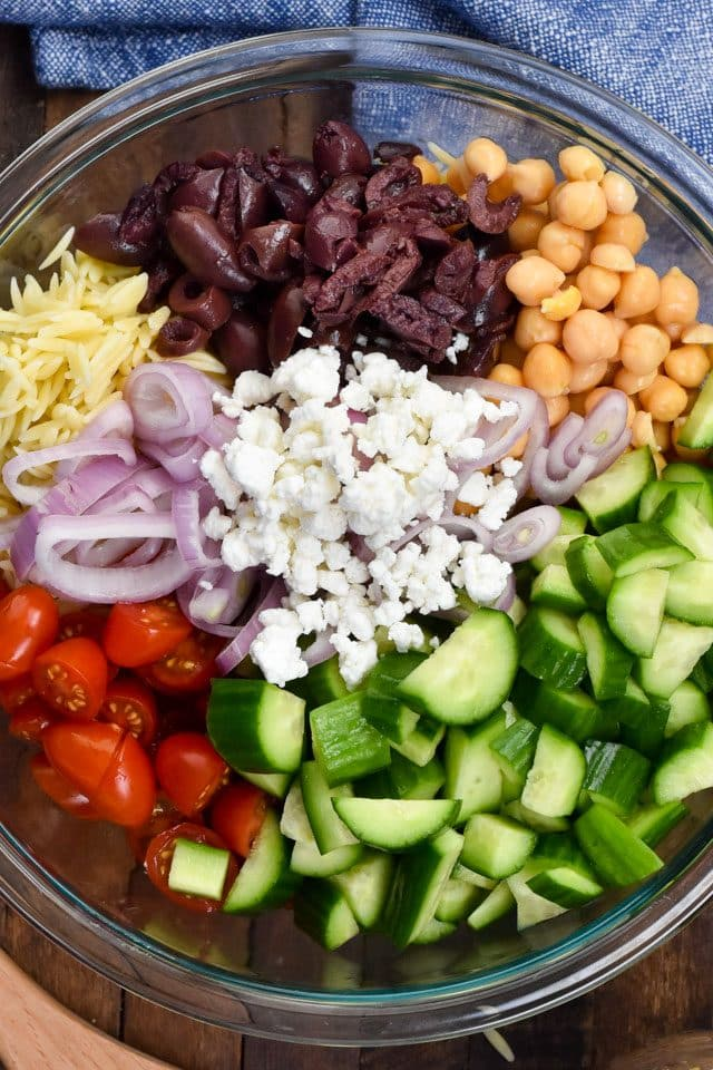 Greek Pasta Salad recipe with lettuce, orzo, cucumber, tomato, garbanzo beans, red onion, olives, and feta