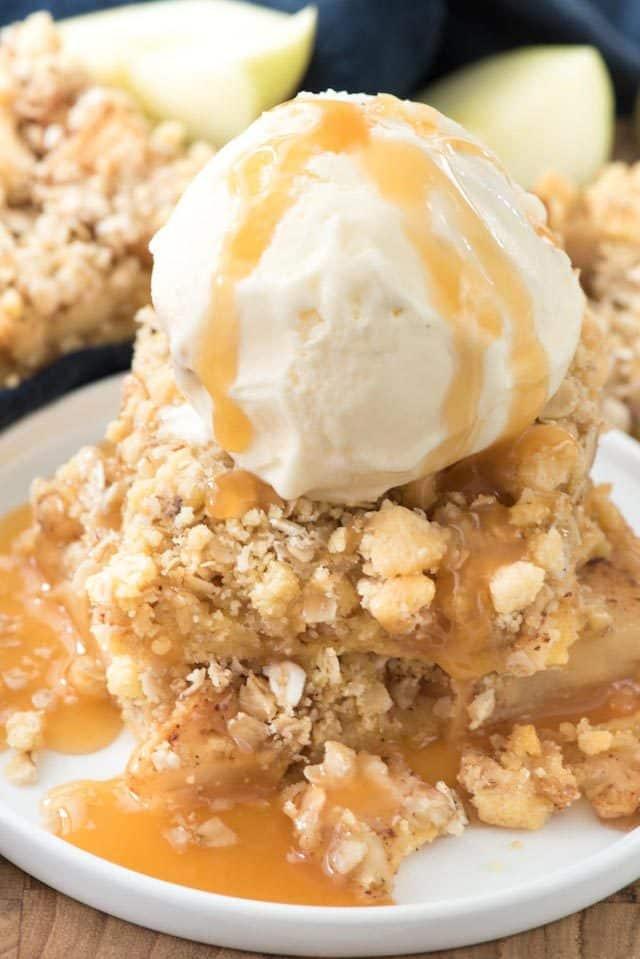 Apple Crumble bar topped with ice cream on a white plate