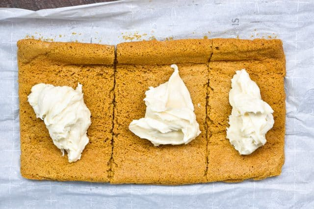 Filling a pumpkin cake roll with cream cheese frosting!
