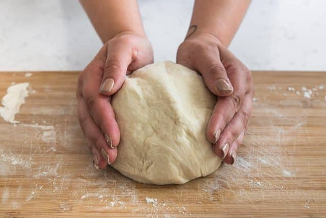 breadstick dough in a ball with hands