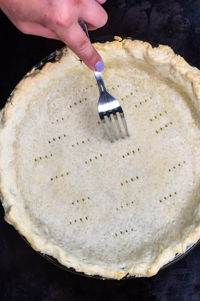 Poking holes in pie crust with fork