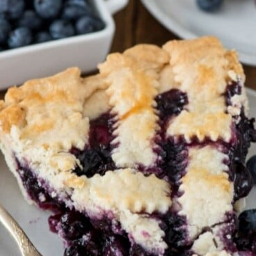 slice of lattice blueberry pie on white plate