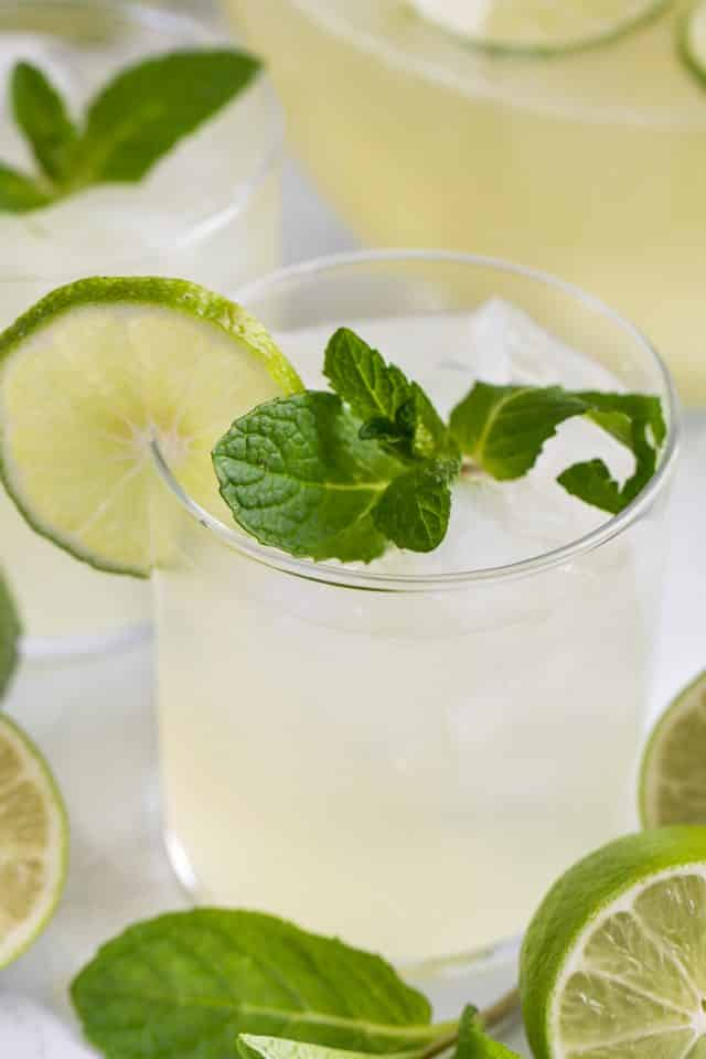 glass of vodka limeade punch with lime and mint