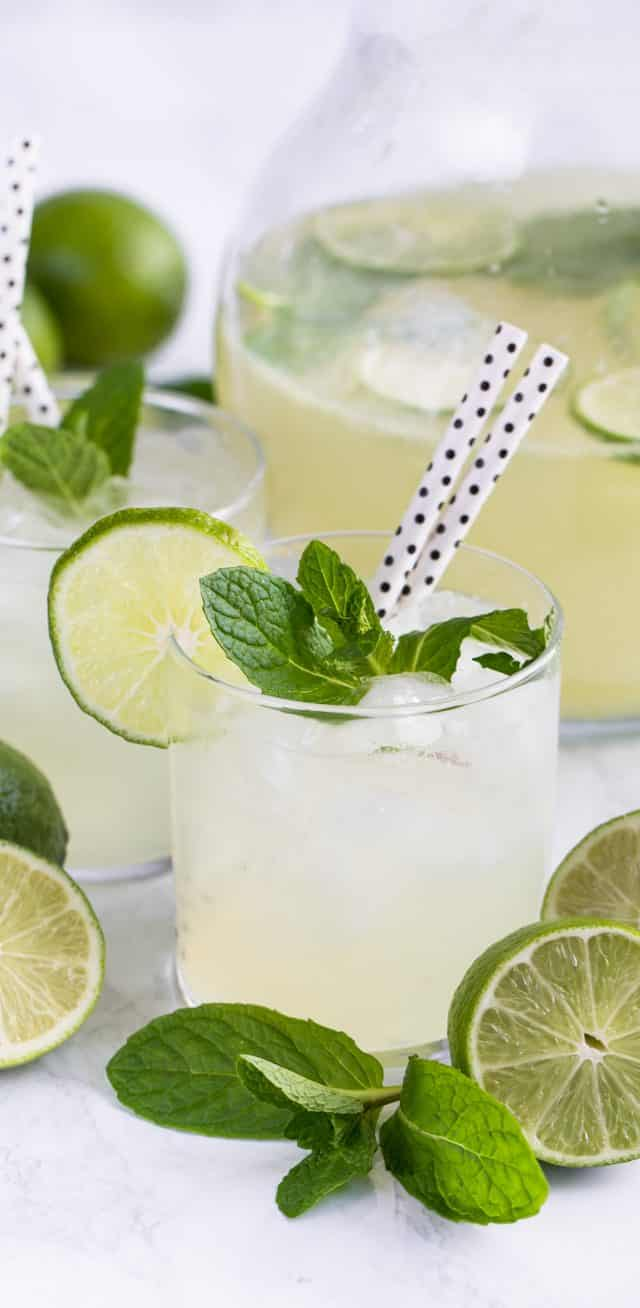 vodka limeade punch in glass with mint limes and straws