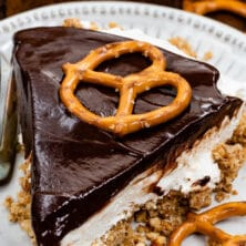 slice of chocolate covered pretzel no bake cheesecake on white plate