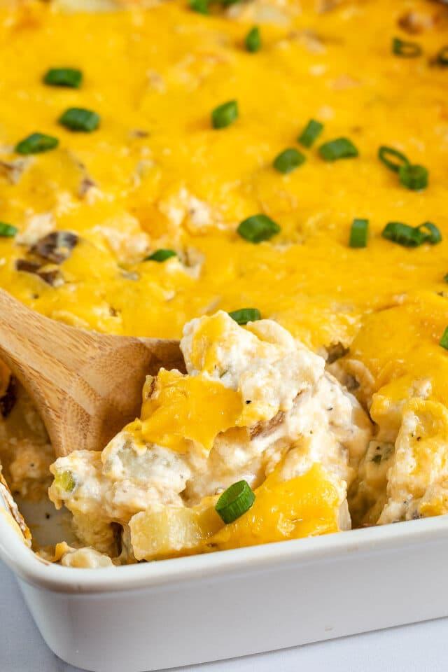 cheesy potatoes on spoon in casserole dish