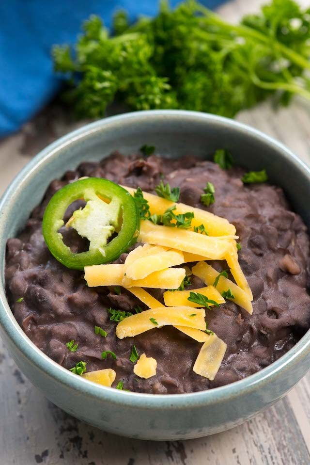 refried black beans in blue bowl