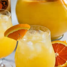 orange vodka party punch in glass and pitcher