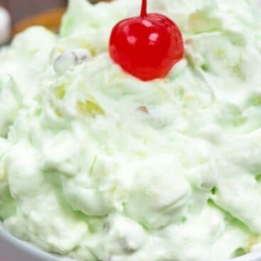 Watergate salad in white bowl with cherry on top