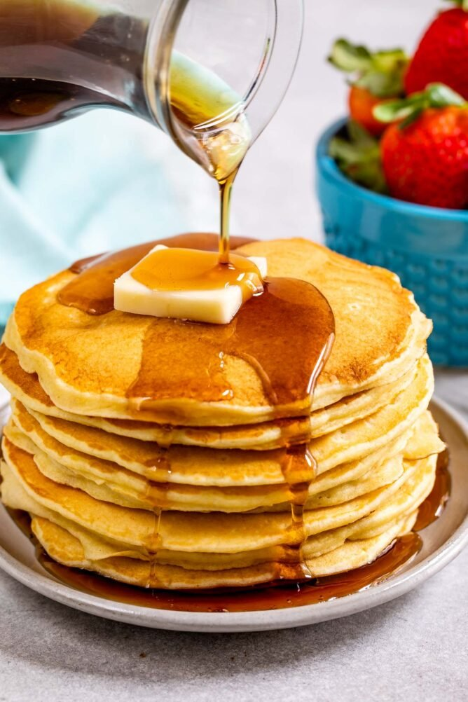 stack of pancakes with butter and syrup being poured over them
