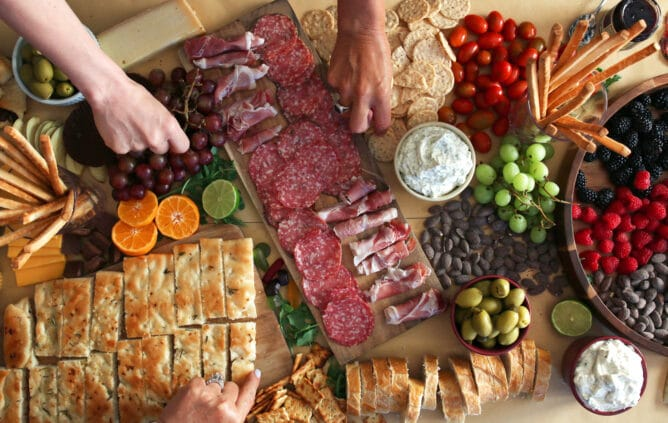 Charcuterie table with meats, breads, fruits, olives and cheese