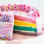 pastel rainbow cake with slice missing