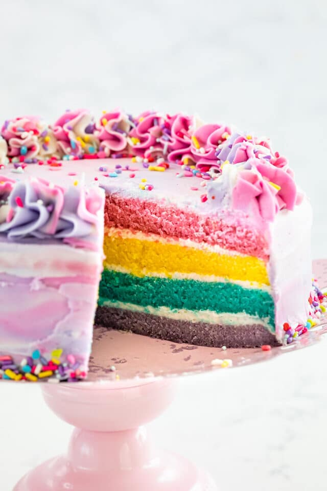 pastel rainbow cake with slice missing