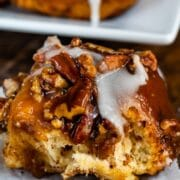 sticky bun with icing on a white plate