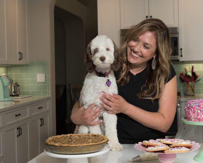 woman holding dog sitting on counter in kitchen behind pies and cookies