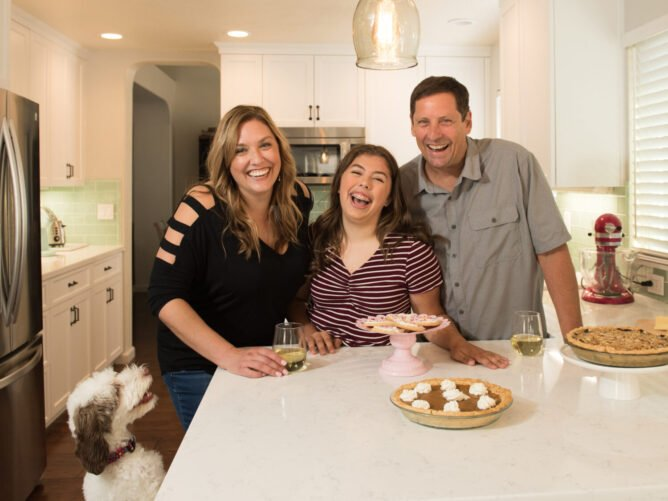 family in kitchen laughing with dog