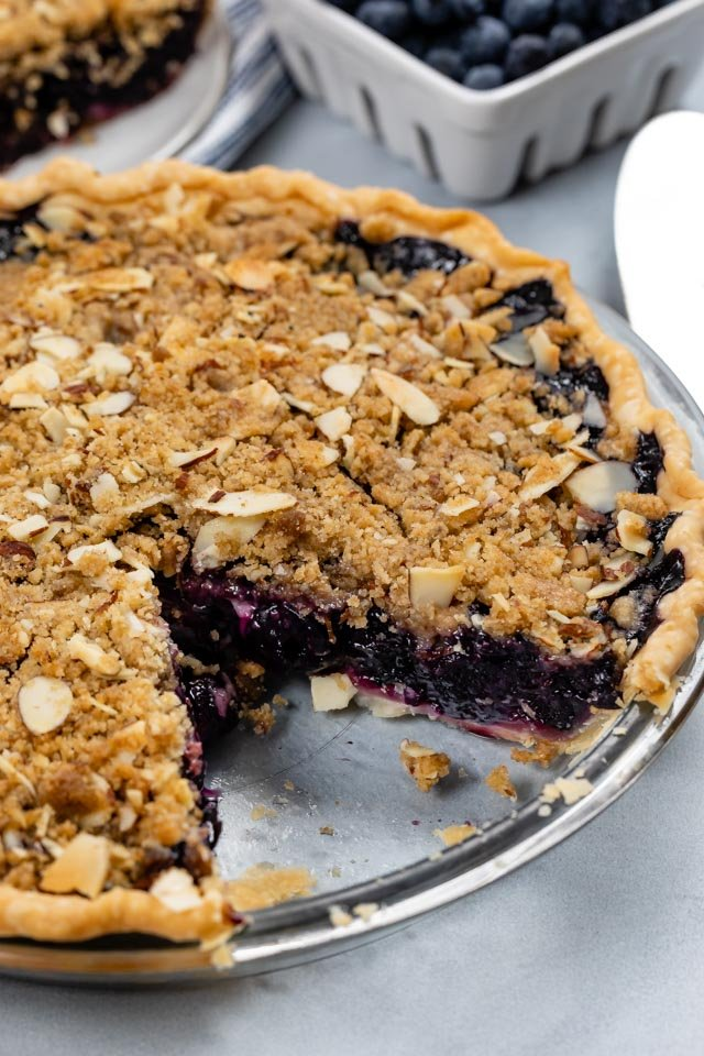 blueberry crumble pie with slice missing