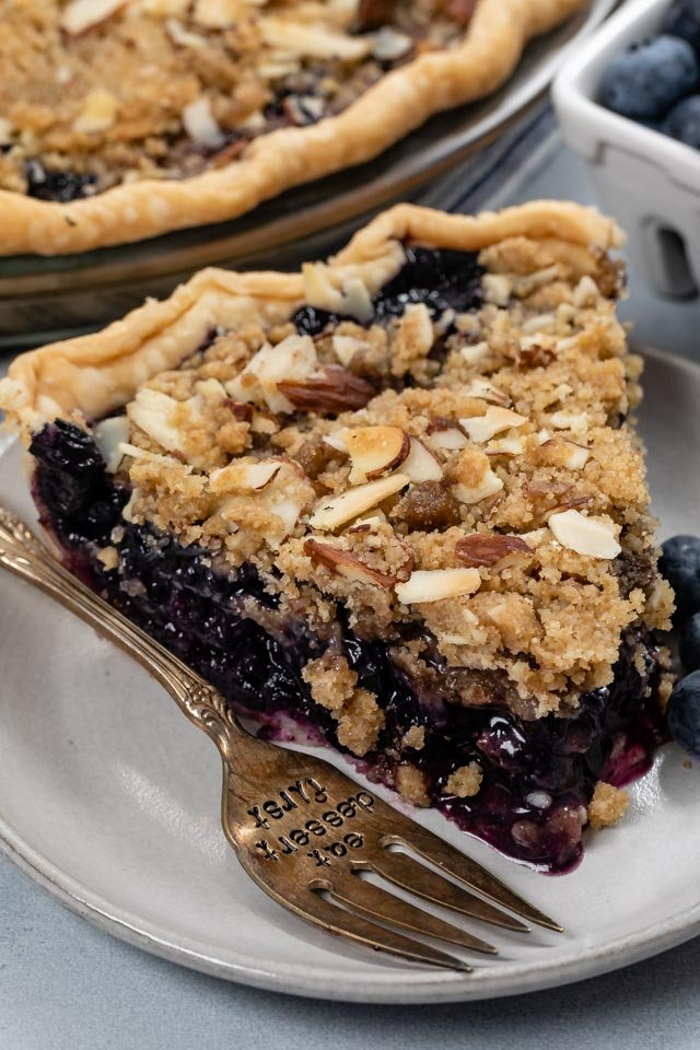 slice of blueberry crumble pie on white plate