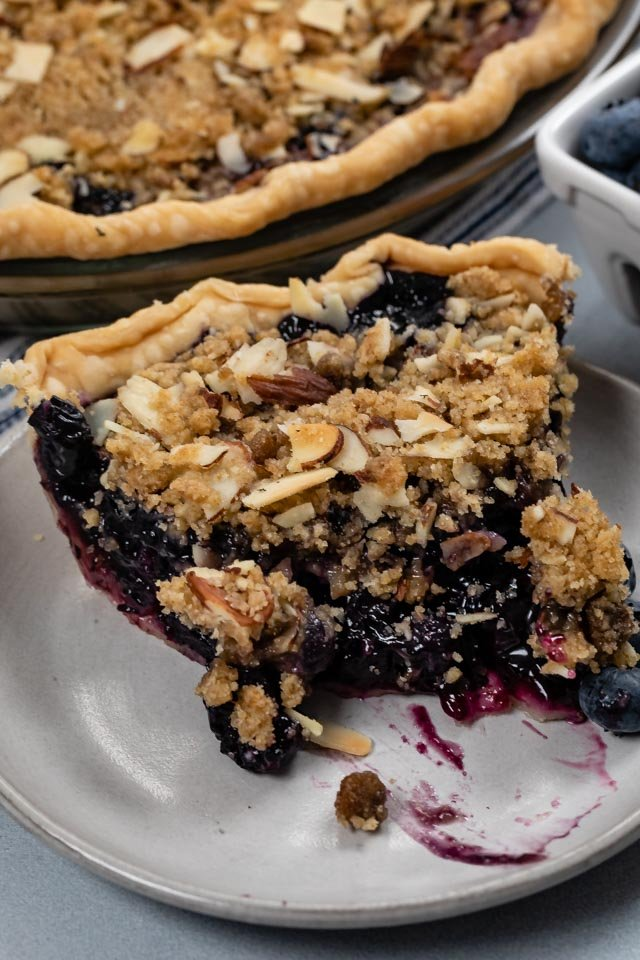 slice of blueberry crumble pie with bite missing
