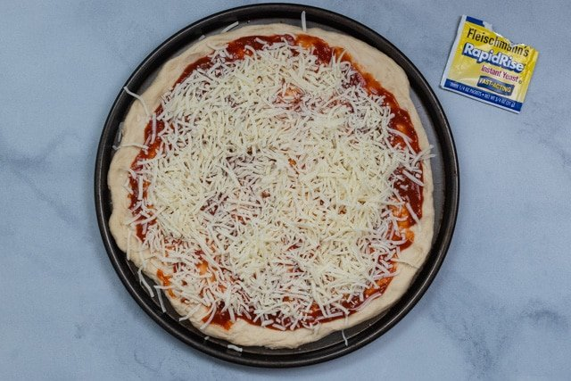 pizza dough with sauce and cheese