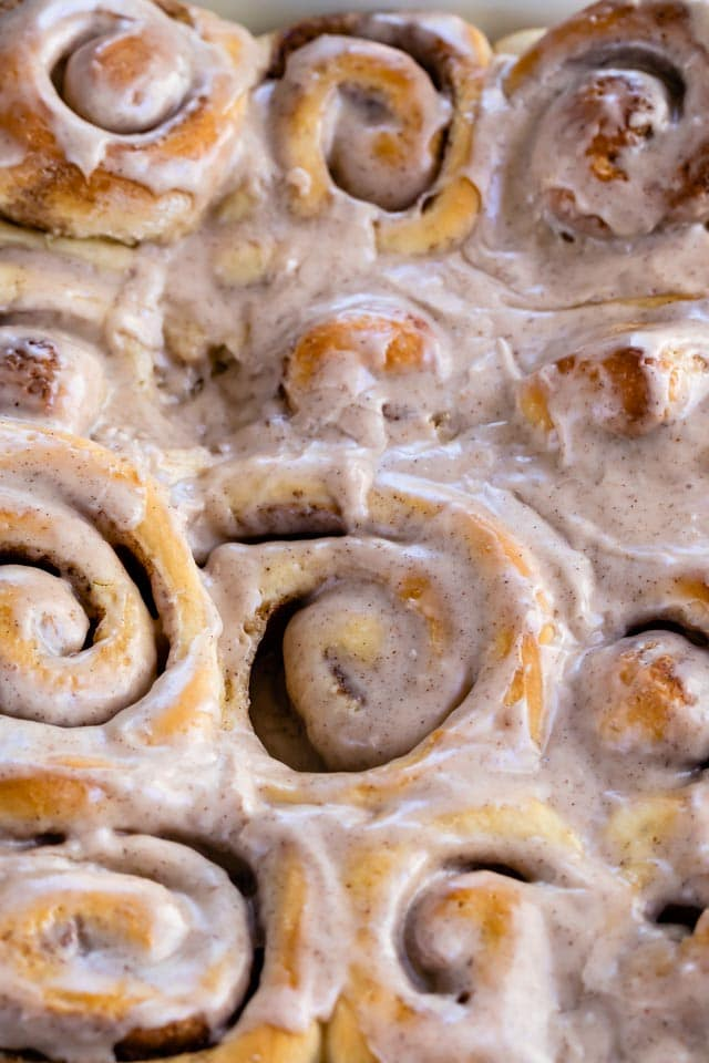 close up of pumpkin spice cinnamon rolls in pan
