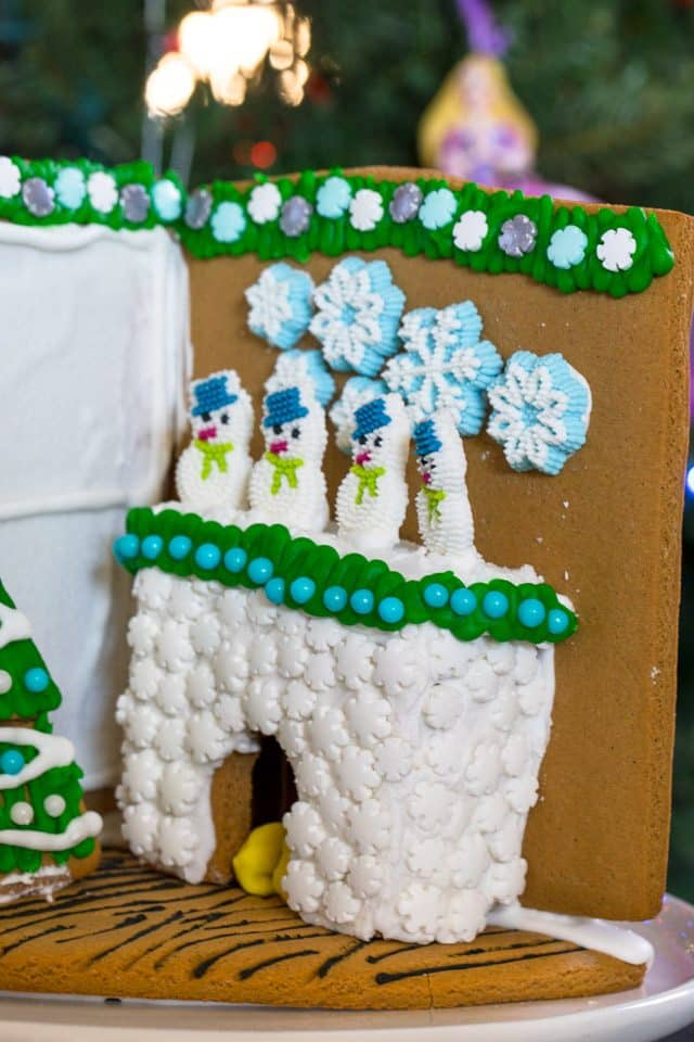 Gingerbread house fireplace with 4 snowmen on the mantel