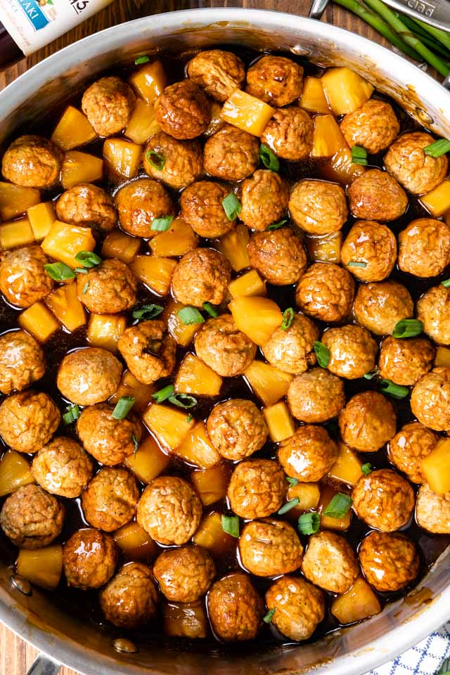 close up overhead shot of teriyaki meatballs with pineapple in pan