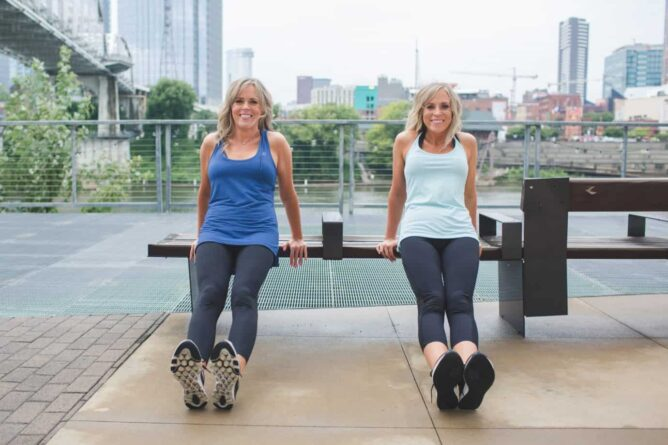 two women exercising on bench with city in the background