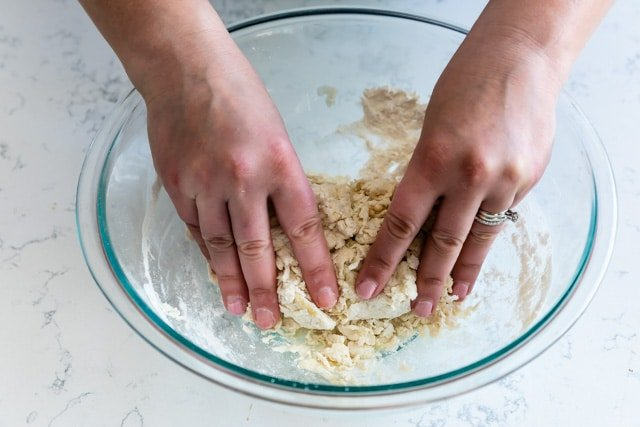 Easy pizza dough with hands in bowl mixing