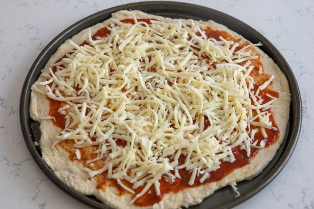 Homemade pizza and crust on pizza pan before cooking