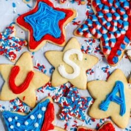 overhead shot of star shaped sugar cookies decorated with red, white and blue frosting