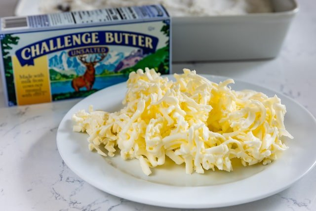 grated butter on white plate with challenge butter box behind