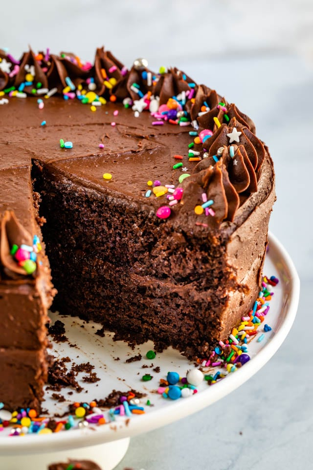 Chocolate layer cake on cake stand with one piece missing