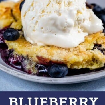 blueberry dump cake with ice cream on plate with color block text below