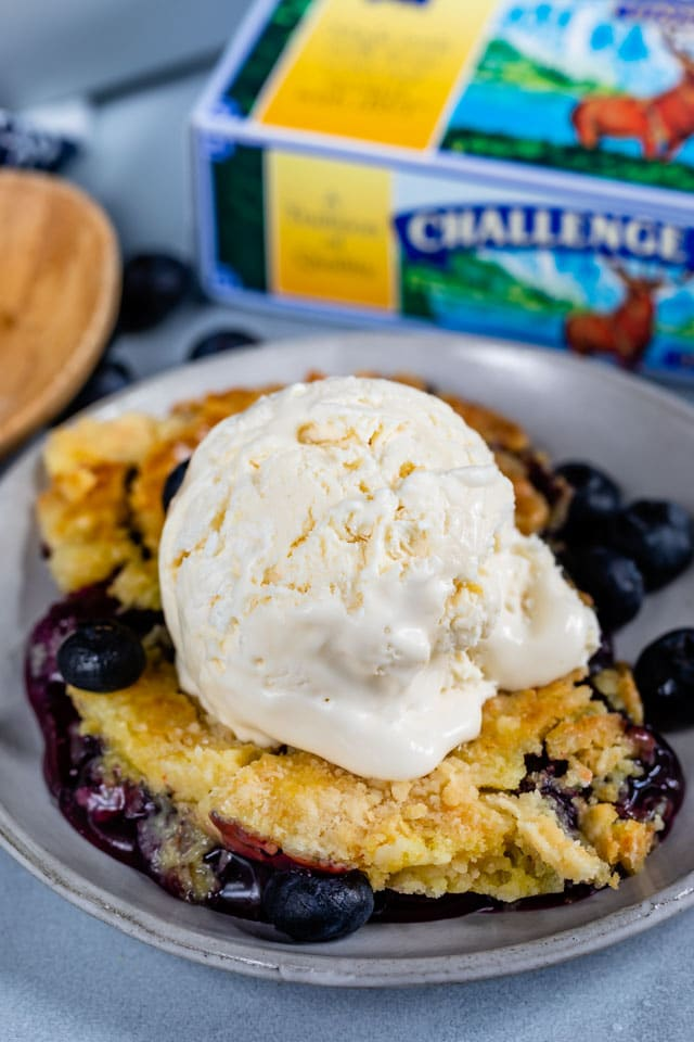 blueberry cobbler ala mode on gray plate with challenge butter box behind
