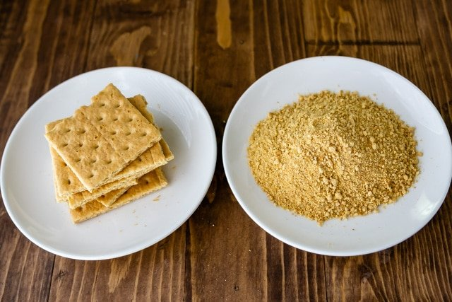 Two white plates with graham crackers and crushed graham crackers on wood table