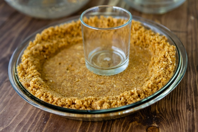 Graham cracker crust being pressed into clear pie dish with glass