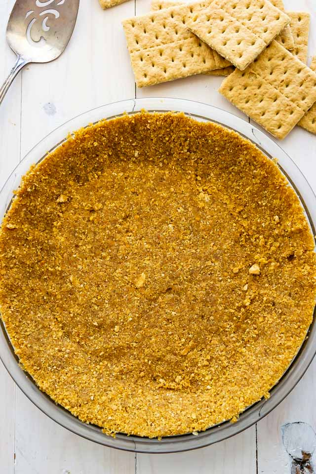 Overhead shot of graham cracker crust in clear pie dish on white wood table with graham crackers and serving silverwear