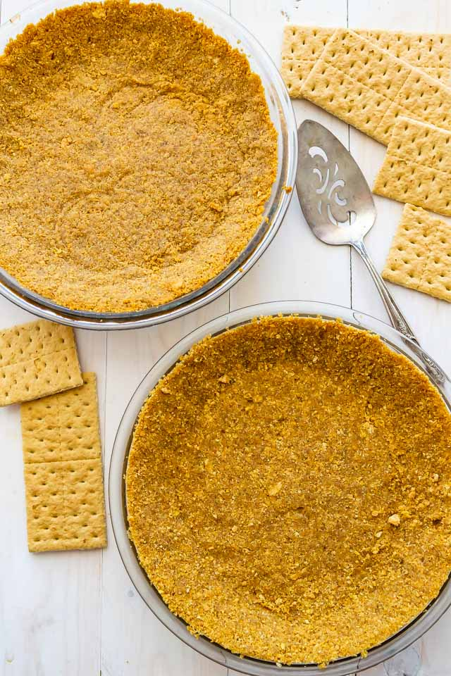 Overhead shot of two graham cracker crusts in pie dishes with graham crackers and a serving