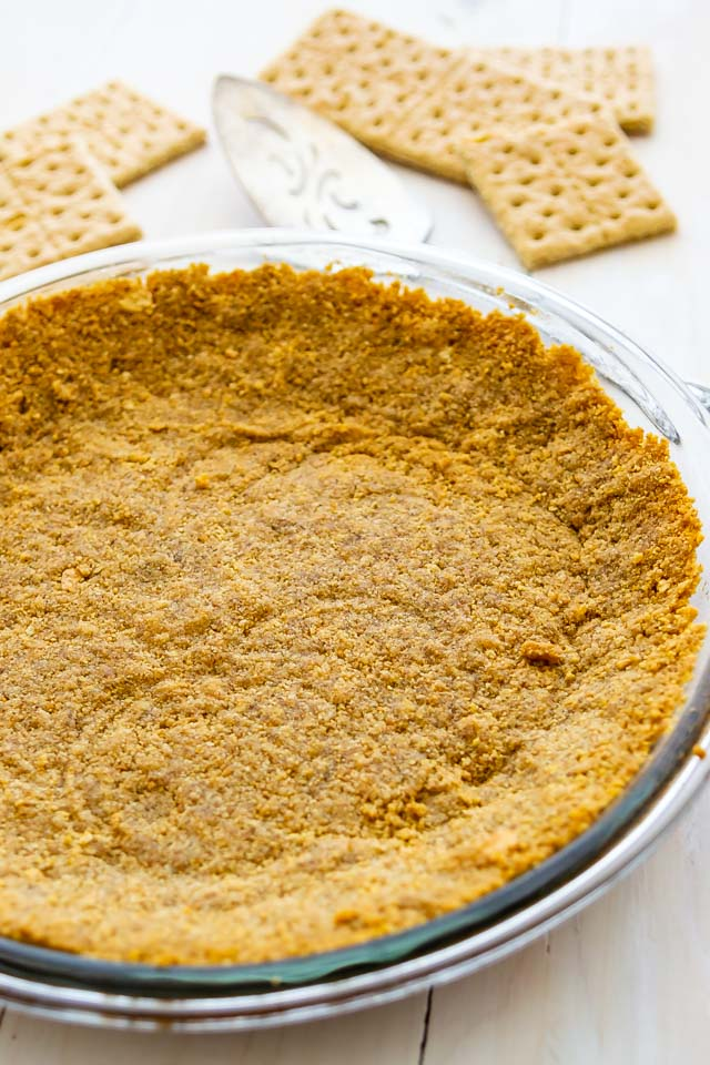 Closeup shot of graham cracker crust in pie dish with graham crackers in the background