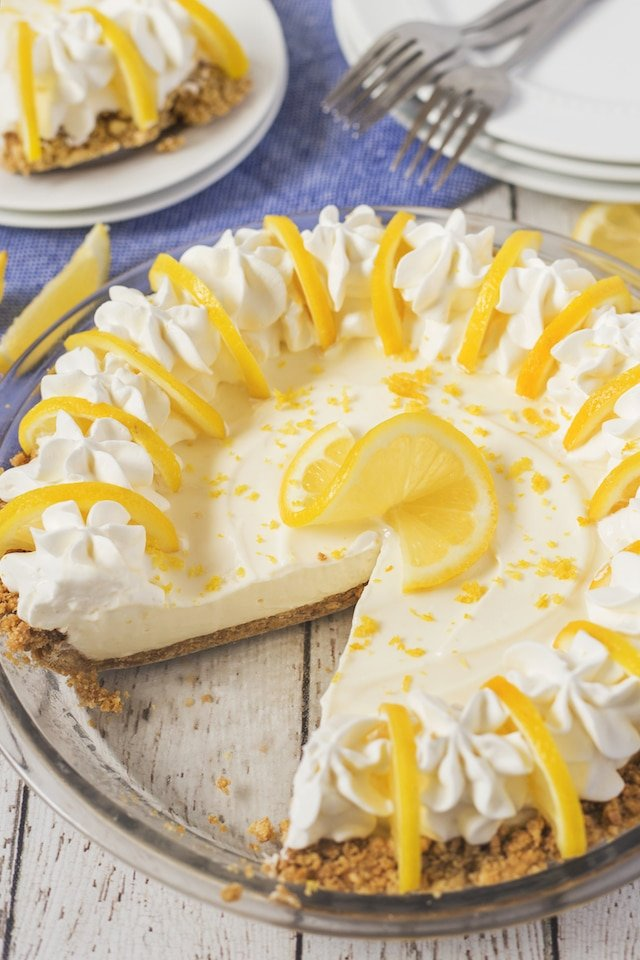No bake lemon pie in a glass pie dish with one slice missing