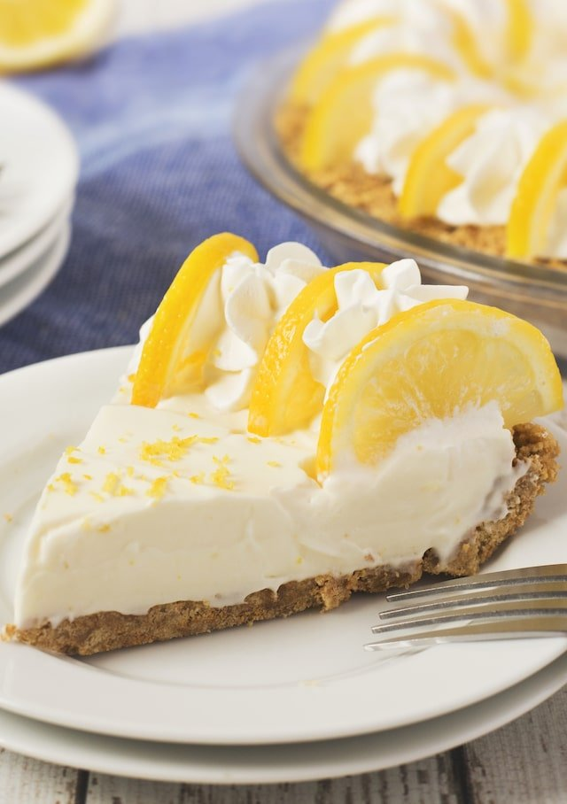 Slice of no bake lemon pie on white plate with fork and rest of pie in background
