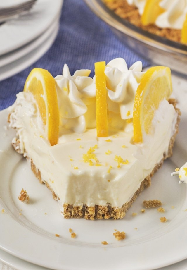 Slice of no bake lemon pie with one bite missing on a white plate