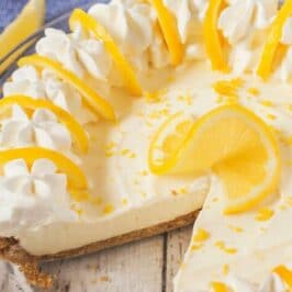 Overhead shot of no bake lemon pie in glass pie dish with one piece missing and recipe title on top of photo in white text