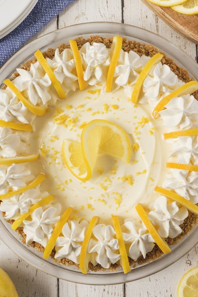 Overhead shot of no bake lemon pie with lemons around it on a white wood table
