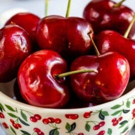 Bowl of cherries with colorblock and blog title on to of image