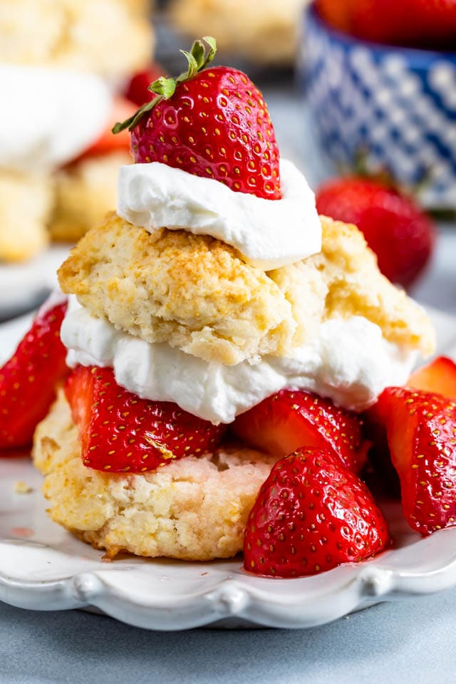 Biscuit strawberry shortcake on white plate with lots of berries and whipped cream